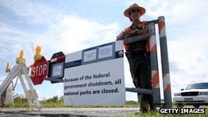 A park ranger stands by the gate of a closed national park in Miami, Florida.