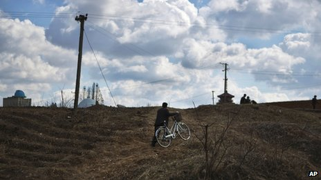 File photo: A North Korean man pushes a bicycle up a hill on the outskirts of Pyongyang, 11 April 2013