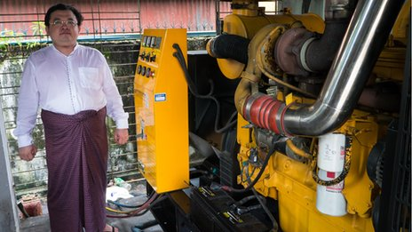 Khin Maung Aye standing next to generators