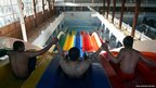 Youths slide down a huge water slide at a public swimming pool in Kabul