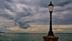 Grey clouds over water, a lamp-post to the right of the picture.