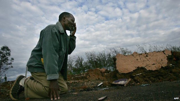 A man who survived an attack on a church where 35 people were burned alive in Kiamba, near the western Kenyan town of Eldoret, weeps as he returns for the first time to the burned out remains of the church on 19 April  2008.