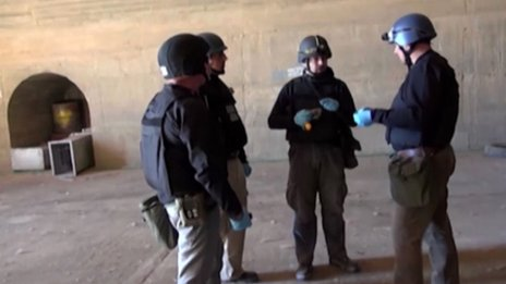 An image grab taken from Syrian television shows inspectors from the Organisation for the Prohibition of Chemical Weapons (OPCW) at work at an undisclosed location in Syria on October 10, 2013