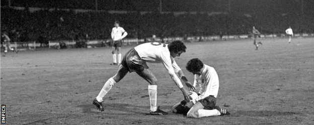 Roy McFarland retrieves the ball from a devastated Norman Hunter after Poland's goal