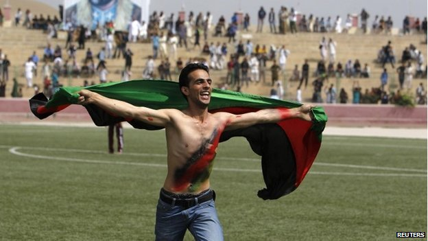 "An Afghan football fan runs with the national flag as he celebrates their national football team""s victory in the South Asian Football Federation Championship, at the Kabul stadium September 12, 2013."