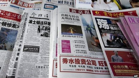 Chinese newspapers with the headlines of Boston Marathon bombings that killed three and wounded more than 170 people, are sold at a newsstand in Beijing, China Wednesday, April 17, 2013.
