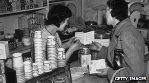 Woman in Grocer's shop holding ration book