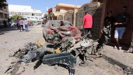 Libyan civilians gather at the site of a car bomb attack outside the building housing the Swedish and Finnish consulates in Benghazi on Friday, 11 October