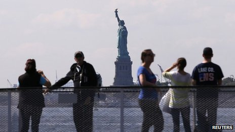 Tourists pause to view the Statue of Liberty from the deck of a Liberty Island ferry boat at Battery Park in New York in this file photo taken  30 September