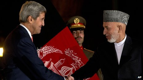 US Secretary of State John Kerry shakes hands with Afghan President Hamid Karzai at a news conference in Kabul, Afghanistan on 12 October 2013