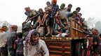 Evacuated Indian villagers get down from a truck at a relief camp as it rains near Berhampur on 12 October 2013
