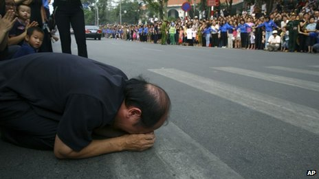 A Vietnamese man knees down and cries while the convoy carrying the coffin of General Giap passes by