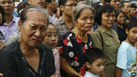 Vietnamese mourners watch as the cortege of General Giap passes by
