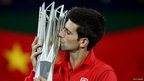 "Novak Djokovic of Serbia poses for photographers with the winner""s trophy"