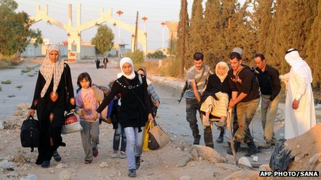 A handout picture released by the official Syrian Arab News Agency (SANA) on 12 October 2013 shows Syrian women and children arriving to be evacuated by Syria's Red Crescent from a Damascus suburb that has been under siege by the Syrian army for months.