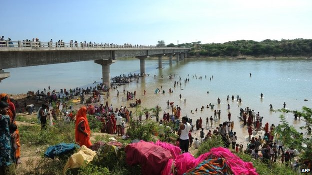 "Hindu pilgrims take a ""holy dip"" in the Sindh river alongside the bridge where a deadly stampede took place the previous day in Madhya Pradesh on October 14, 2103"