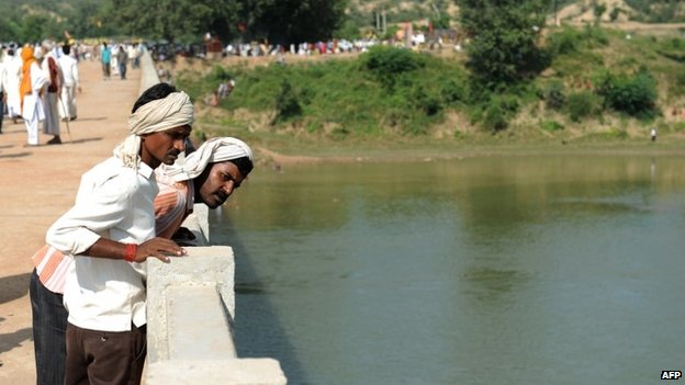 Hindu pilgrims look down at the Sindh river as they stand on the bridge where a deadly stampede took place the previous day on October 14, 2103