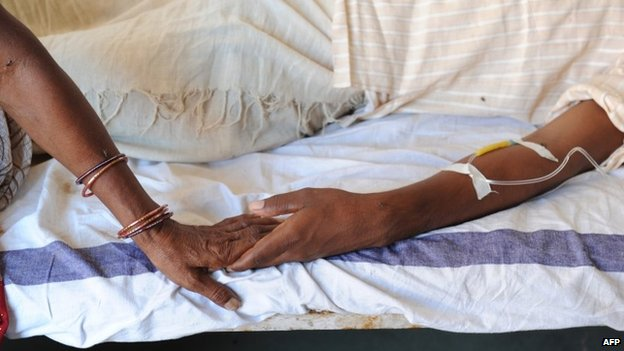 An Indian Hindu pilgrim    holds her injured son's hand at a hospital at Seondha