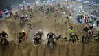 Riders reach the crest of a dune during the opening lap of the main race at the RHL Weston beach race