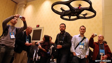 People looking at a drone controlled by an iPhone, shown in Nevada in 2010