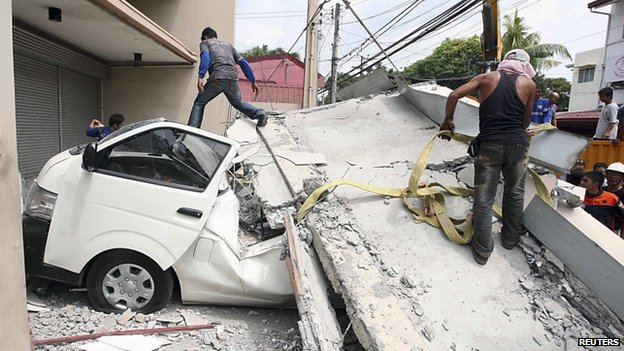 Workers use a crane to lift up concrete block that fell on a car after buildings collapsed during an earthquake in Cebu city, central Philippines, 15 October 2013