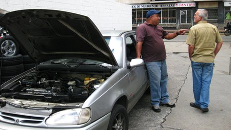 Daniel (left) stands next to his car at a petrol station in Caracas, Venezuela in September 2013