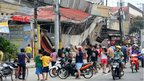 People gather on the street next to damaged buildings in Cebu City, Philippines