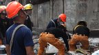 Rescuers shift through the rubble to recover an unidentified man