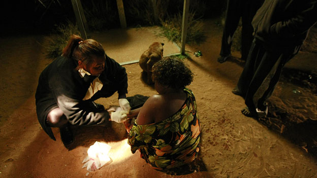 Ros Forester (L) of Tangentyere council night patrol assists an intoxicated Aboriginal woman who had been stabbed during a domestic dispute in a town camp outside the central Australian town of Alice Springs in this picture taken July 5, 2007
