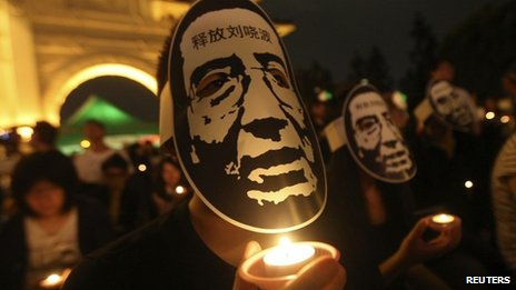 Activists wearing masks of China's jailed Nobel laureate Liu Xiaobo hold candles during a night vigil in Taipei