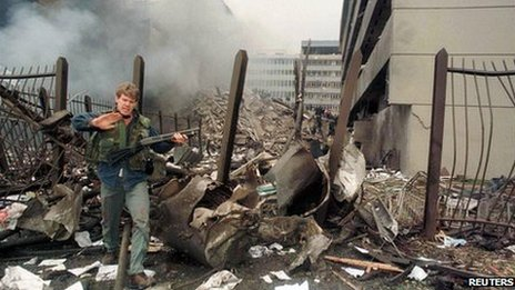 A US embassy official secures the area around the embassy building after a powerful bomb blast in Nairobi (7 August 1998)