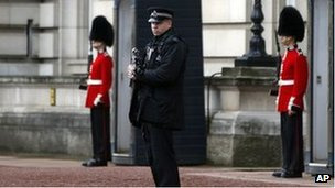 A British police officer guards the grounds of Buckingham Palace in central London, Monday, Oct. 14, 2013