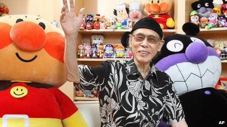 Takashi Yanase, creator of one of Japan's most beloved cartoon characters, Anpanman, waves accompanied by Anpanman, left, and Baikinman