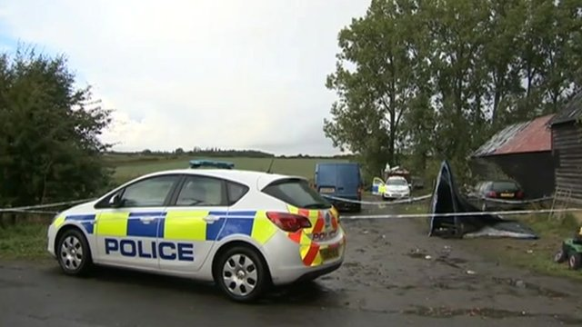 Police car at Begwary barn, scene of stabbings