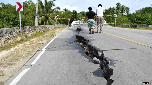 Residents walk along huge cracks in a road after an earthquake struck Bohol province, central Philippines, October 15, 2013.