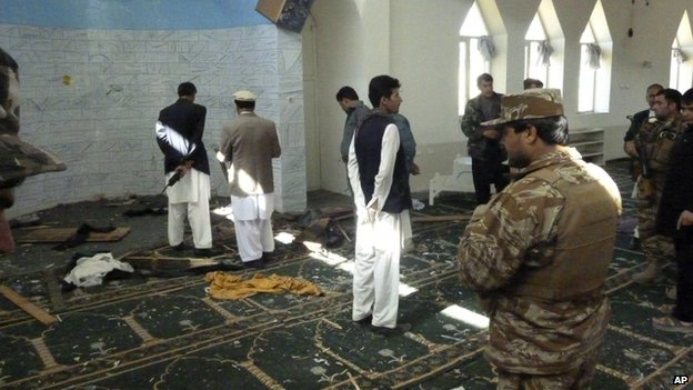 Afghan police and officials examine the mosque in Puli Alam, Logar Province, where a bomb hidden in the base of a microphone killed Afghan Governor Arsallah Jamal on 15 October