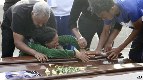A survivor cries on the casket of her sister who died when their boat capsized off in the Canal of Sicily