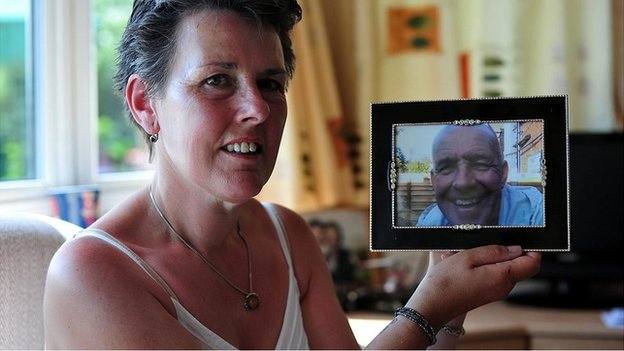 Tanya holds a picture of her husband Gary who was murdered by their son