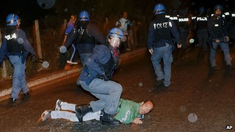 A policeman in riot gear subdues a man during a protest outside the Society of St Pius X headquarters, a schismatic Catholic group, where the funeral of former Nazi war-criminal Erich Priebke was scheduled to take place in Albano Laziale, in the outskirts of Rome, Tuesday, Oct. 15, 2013