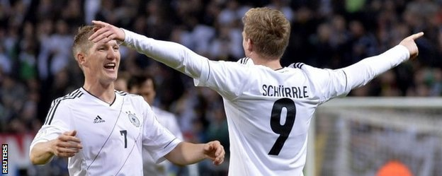 Andre Schurrle celebrates a goal with Bastian Schweinsteiger, who was winning his 100th cap