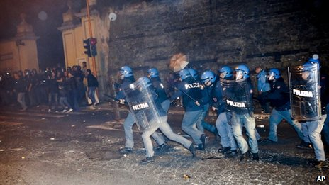 Policemen in riot gear chase after protesters outside the Society of St. Pius X headquarters, a schismatic Catholic group, where the funeral of former Nazi war-criminal Erich Priebke was scheduled to take place in Albano Laziale, in the outskirts of Rome, Tuesday, Oct. 15, 2013