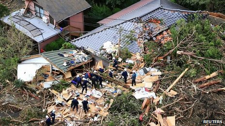 Rescue workers search among collapsed houses following a landslide caused by Typhoon Wipha on Izu Oshima island, south of Tokyo, 16 October 2013