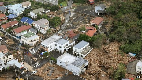 Several houses in a residential area  are covered by debris from mudslides after a powerful typhoon hit Izu Oshima island on 16 October 2013