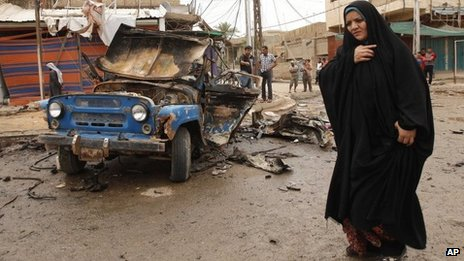 An Iraqi woman walks past a bomb-damaged vehicle in Baghdad (20 May 2013)