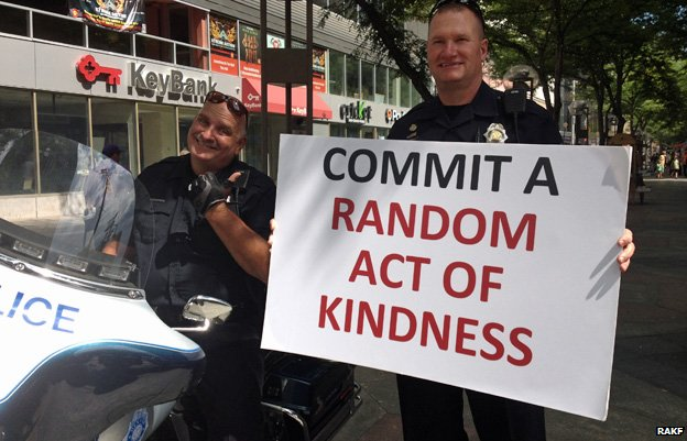 "Police officers holding sign that reads ""Commit a random act of kindness"" - photo from Random Acts of Kindness Foundation"