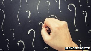 Hand  writing question marks on blackboard