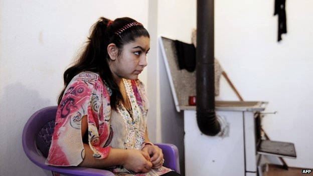 Leonarda Dibrani sits at her home with her family members in the town of Mitrovica, Kosovo, 16 October