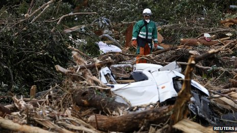 A rescue worker looks for a victim of a landslide caused by Typhoon Wipha in Izu Oshima island, south of Tokyo, 17 October 2013
