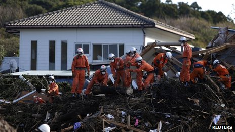 Rescue workers look for victims at a site that is damaged by a landslide caused by Typhoon Wipha in Izu Oshima island, south of Tokyo, 17 October 2013