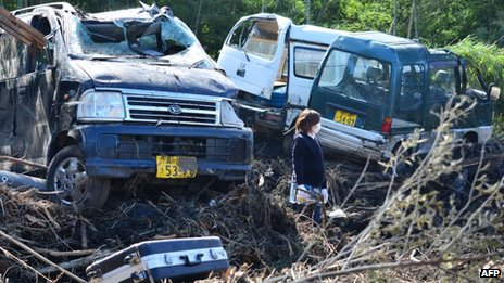 A woman stands next to a damaged vehicles after a landslide buried houses caused by heavy rains brought on by typhoon Wipha at Oshima island, 17 October 2013